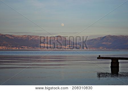 Wooden dock in the sea whit mountain and hills as background