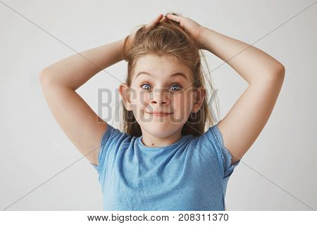 Funny cheerful blonde girl with blue eyes holding hair with hands, looking in camera with raised brows and silly face expression.