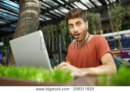 Shot of amazed bearded caucasian man with dark hair dressed casually looking at the screen of his notebook recieving message being shocked to forget about important meeting.