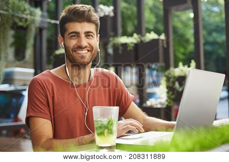 Portrait of bearded male employee wearing white earphones, typing on keyboard on generic laptop, working outdoors. Businessman checking e-mail sitting at table with notebook during lunch break at summer cafe.
