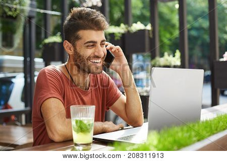 Attractive bearded male with dark hair and stylish hairstyle having conversation over smart phone looking on the screen of laptop with smile planning meeting with his friend. Modern techologies, communication.