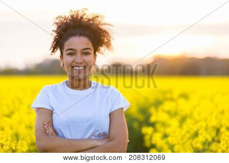 Beautiful mixed race African American girl teenager female young woman happy smiling with perfect teeth at the end of a path in a field of yellow flowers
