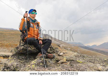 A lonely tourist with a backpack and sticks for movement in the mountains. In sunglasses and with a backpack rest sidiya on a stone