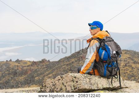 A lonely tourist with a backpack and sticks for movement in the mountains. In sunglasses and with a backpack rest sidiya on a stone. View from the back