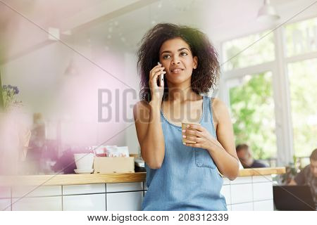 Young attractive dark-skinned university student with dark wavy hair in casual blue shirt talking on phone with her boyfriend, looking aside with calm expression, drinking coffee relaxing after study in cafe