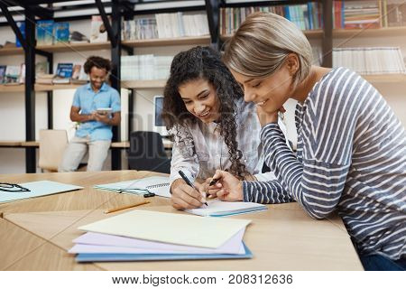 Close up of pair beautiful young multi-ethnic student girls doing homework together, writing essay for presentation, preparing for exams with good mood.
