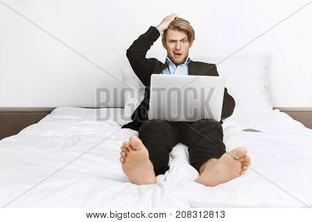 Beautiful blonde unshaved businessman lying in bed, working on laptop computer, holding hand on head with shocked expression after making mistake in calculations