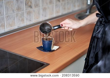 A picture of a young wife preparing coffee in the kitchen in the morning.