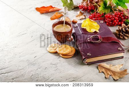 Autumn still life with cup coffee book and dry leaf on stone surface with copyspace.
