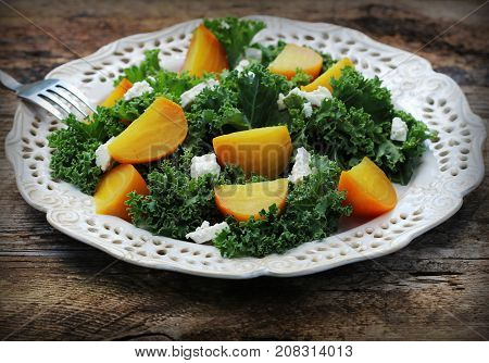 Healthy beet salad with fresh kale lettuce, nuts, feta cheese on wooden background .