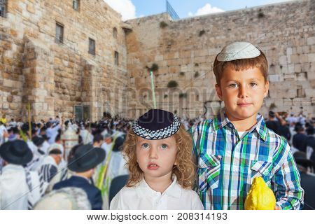 Two Jewish boys in skullcap with etrog. Autumn Jewish holiday Sukkot.  The greatest shrine of Judaism is the Western Wall of the Temple