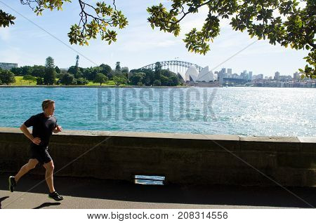 SYDNEY - AUGUST 11 2017:Australian man runs near the Opera House. Approximately 35% of the Australian population participated at least in one physical recreation activity.