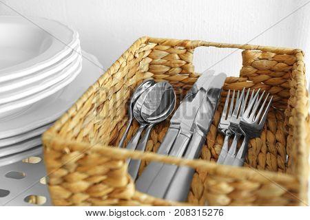 Cutlery in wicker basket on shelf