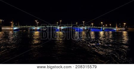 Night cityscape with river and bridge in Saint-Petersburg . Lantern lights on the bridge .