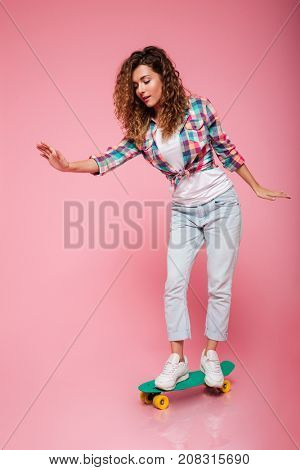 Young serious concentrated playful lady riding skateboard isolated over pink
