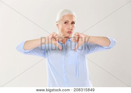Displeased serious old woman showing thumb down and looking at the camera over white background