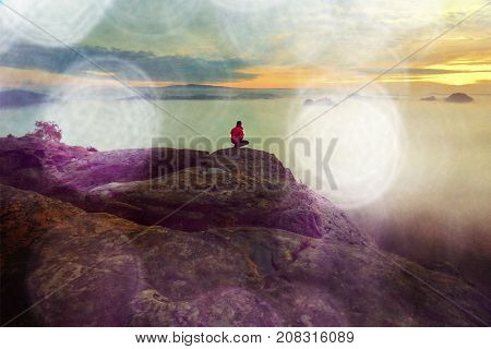 Hiker In Squatting Position On Peak Of Rock And Watching Into Colorful Mist And Fog