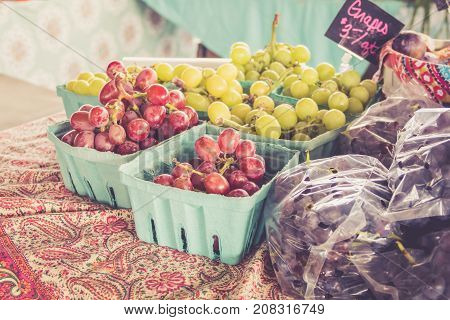 Farm fresh grapes and vegetables on display at farmers market harvest festival