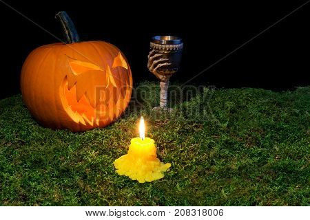 Halloween Pumpkin, Goblet And Candles Glowing In The Dark On A Forest Moss.