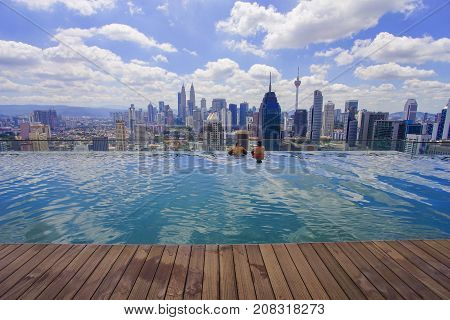 Unidentified Businessman And Traveller Swimming In Infinity Pool With Kuala Lumpur City Skyline And