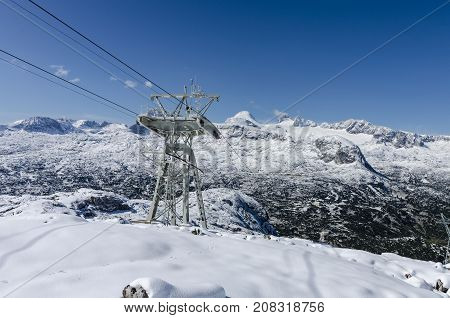 Snowy landscape - the view to the Dachstein top from the hiking track to Krippenstein with a cablecar track and a trestle