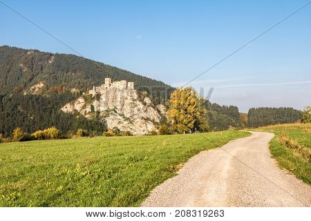 Ruins Of Strecno Castle In Autumn Landscape With Dirt Road