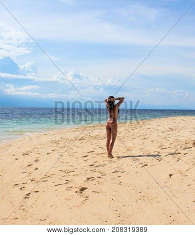 Woman on sunny beach. Tropical beach photo. Beautiful girl on beach. Young woman in bikini under sunshine. Tropical island paradise holiday travel. White sand beach and blue seawater. Sunbathing girl