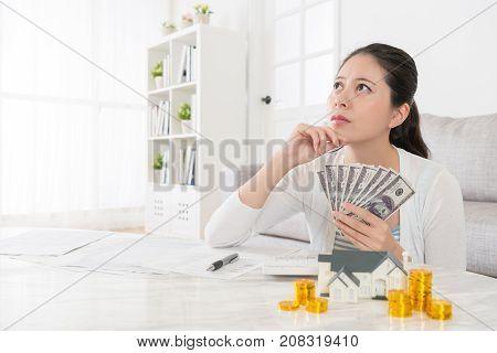 Woman Holding Cash Thinking Buying New House