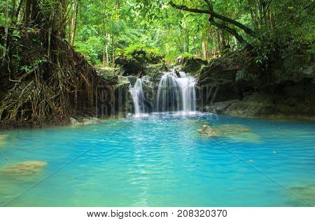 Blue lake and small waterfall. Bright exotic nature with fresh water stream. Dark green trees and white waterfall under cloudy sky. Turquoise blue lake and river in bush. Travel in Asia photo