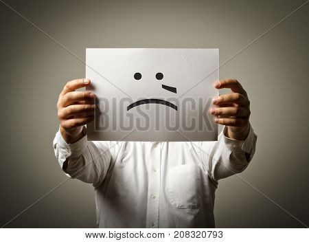 Man is holding white paper with smile. Crying and trouble concept.