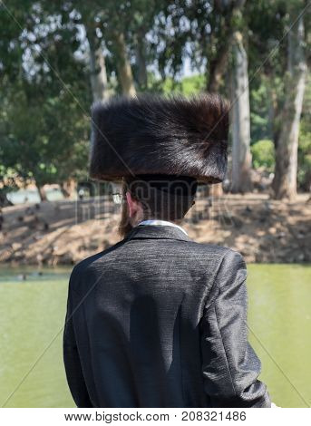 Undefined orthodox jewish man looking on pond in municipal park. Israel
