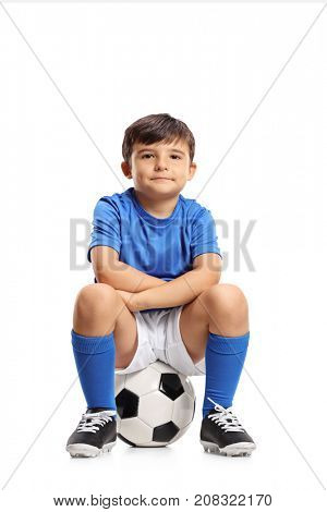 Boy in a blue jersey sitting on a football and looking at the camera isolated on white background