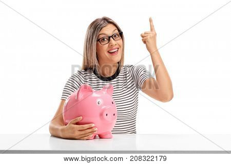 Young woman with a piggybank seated at a table pointing up isolated on white background