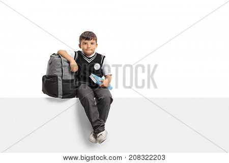 Schoolboy with a backpack and a book sitting on a panel and looking at the camera isolated on white background