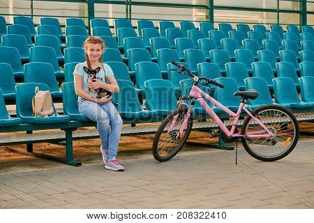 smiling girl relaxing with dog Chihuahua. Sporty kid posing with a Bicycle. girl in the blue seats of the stadium.