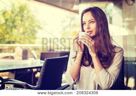 beautiful young girl sitting alone in a cafe drinks coffee, outdoor