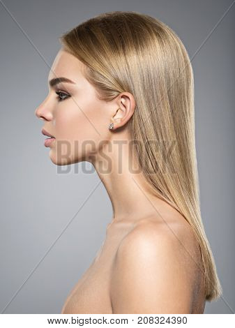 Profile portrait of  a beautiful young woman with long light straight  hair.