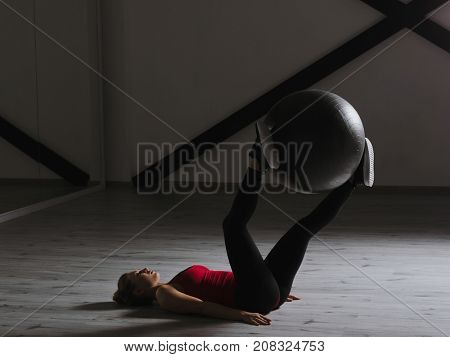 Young girl doing exercises with fit ball at studio