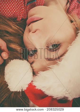 Happy woman waiting for Christmas season wearing pajamas and Santa Claus hat lying in bed.