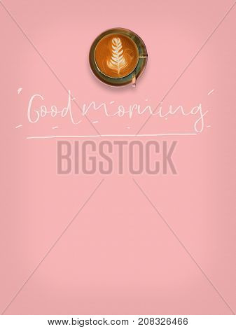 Top view of hot coffee cup on pink background with text good morning.