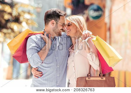 Beautiful young couple enjoying in shopping having fun in the city.Consumerism love dating lifestyle concept.