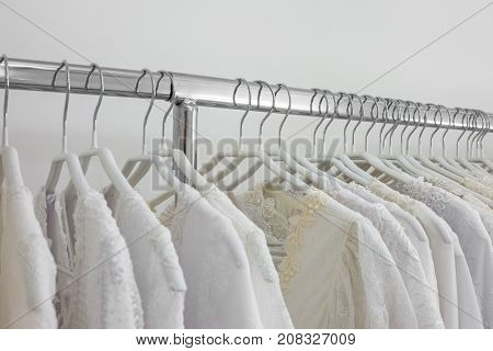 Beautiful bridal dress on a hangers. Wedding dresses in bridal salon.