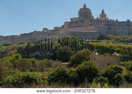 Ancient hilltop fortified capital city of Malta, The Silent City, Mdina or L-Imdina, it's skyline against blue Spring skies with huge walls, domes and towers, over fields of spring flowers, March 2017