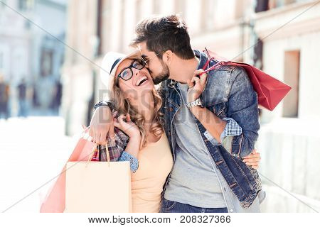 Sale, consumerism and people concept - happy young couple with shopping bags walking in city.