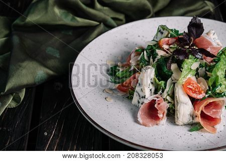 Green salad with prosciutto and blue cheese served with fabric on dark wooden background
