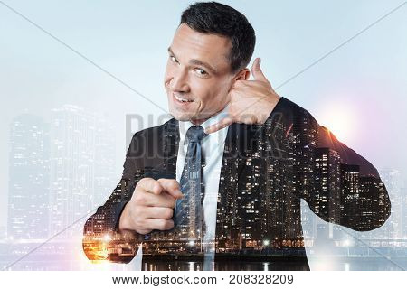 You next. Close up of experienced pleasant manager keeping his hand near ear while pointing at you and expressing cheer