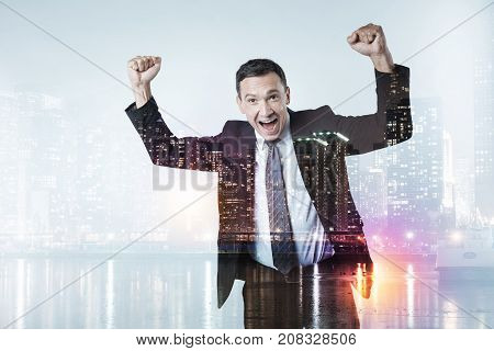 Always winning. Waist up of cheerful businessman standing and keeping his fists raised up while expressing endless happiness