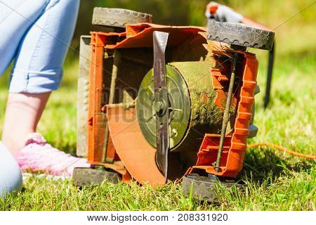 Gardening. Female person gardener mowing green lawn with lawnmower having problem with broken mower