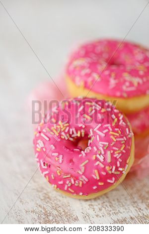 pink donut. three pink donuts on a light worn wooden background