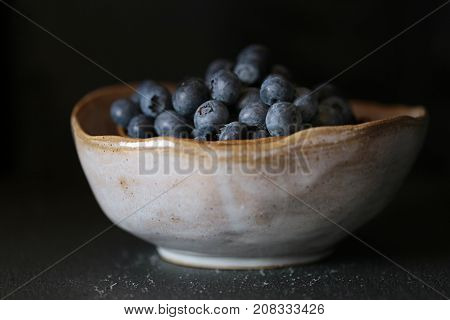 Blueberry . ripe blueberries in a gray clay cup on a black background. Dark Key. The harvest of blueberries